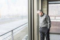 Homme d'affaires, appuyé contre la fenêtre — Photo de stock