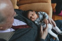 Newborn baby girl on lap of great-granddaughter at home — Stock Photo