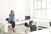 Casual donna di affari che si siede sulla scrivania in ufficio e che guarda l'obbiettivo — Foto stock