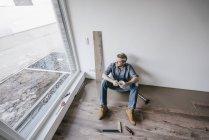 Homem maduro montagem piso em nova casa, beber café e fazer uma pausa — Fotografia de Stock