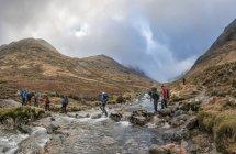 Nepal, Himalayas, Khumbu, Everest region. Trekkers crossing mountain stream — Stock Photo