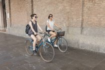 Two young women riding bicycles in city — Stock Photo