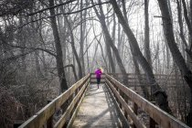 Woman running on wooden bridge through forest — Stock Photo