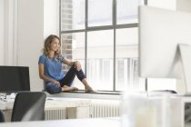 Lässige Geschäftsfrau auf der Fensterbank im Büro sitzen — Stockfoto