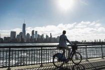 Мужчина на велосипеде в Нью-Джерси на набережной с видом на Манхэттен, США — стоковое фото