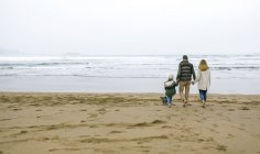 Spain, Asturias, Back view of unrecognizable family walking barefoot by the beach with the sea on background — Stock Photo