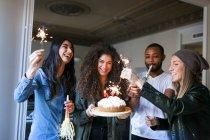 Porträt von jungen Freunden feiert Geburtstag mit Torte und Wunderkerzen — Stockfoto