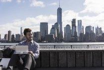 Людина за допомогою планшетного ПК в Нью-Джерсі набережній з видом на Манхеттен, США — стокове фото