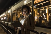 Portrait of smiling young woman with headphones and tablet standing at the tram stop — Stock Photo