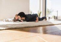 Отец и маленький сын играют ползая по ковру дома — стоковое фото