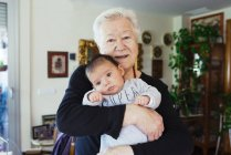 Portrait of smiling great-grandmother holding baby — Stock Photo