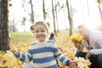 Happy girl with family in autumnal forest — Stock Photo