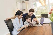 Familia con ordenador portátil y la guía para la planificación de vacaciones en casa - foto de stock