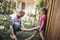 Pai aplicando protetor solar nas pernas da filha no jardim — Fotografia de Stock