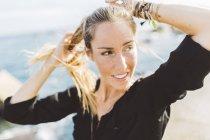 Улыбающаяся молодая женщина смотрит вокруг на набережной — стоковое фото