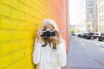 Портрет пожилой женщины, фотографирующей у оранжевой стены — стоковое фото