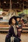 Donna in piedi con la bambina sulla fiera e guardando la fotocamera — Foto stock