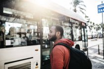 Spain, Barcelona. Portrait of young black guy in casual clothing, waiting for the bus. — Stock Photo