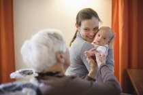 Happy old woman meeting granddaughter and great-granddaughter — Stock Photo