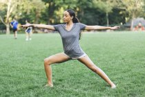 Young attractive african american woman doing stretching at park — Stock Photo