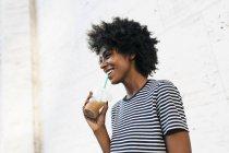Joven atractivo africano americano mujer beber bebida de taza por paja - foto de stock