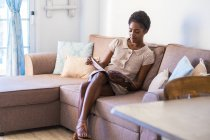 Attractive black woman reading magazine at couch — Stock Photo