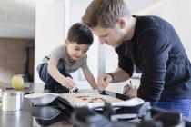 Père et fils préparent ensemble une pizza dans la cuisine — Photo de stock