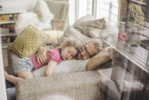 Father relaxing with daughter on sofa at home — Stock Photo