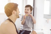 Happy father and son brushing teeth together in bathroom — Stock Photo