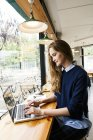 Side portrait of young woman using laptop in cafe — Stock Photo