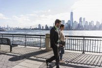USA, colleagues walking at New Jersey, waterfront with view to Manhattan — Stock Photo