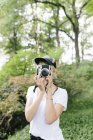 Молодая женщина фотографирует на винтажную камеру в Центральном парке, Манхэттен, Нью-Йорк США — стоковое фото