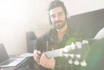 Mann spielt Gitarre auf Sofa — Stockfoto