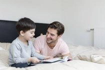 Glücklicher Vater und Sohn ein Buch im Bett lesen — Stockfoto