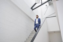 Smiling businessman walking downstairs in office building — Stock Photo