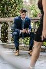Portrait d'un homme d'affaires assis à la table de la rue et utilisant un smartphone — Photo de stock