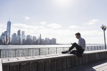 Man using tablet at New Jersey waterfront with view to Manhattan, New York City, USA — Stock Photo
