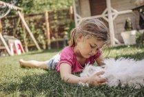 Menina deitada no gramado no jardim com cão — Fotografia de Stock