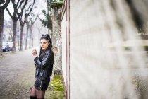 Bruna giovane donna vestita di sigaretta nera fumante — Foto stock