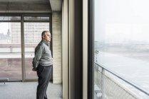 Homme d'affaires, regarde par la fenêtre — Photo de stock