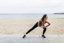 Young woman stretching and warming up for training at beach — Stock Photo