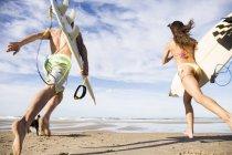 Задній вид серферів пара з дошки для серфінгу, працює в океан біля піщаного пляжу — стокове фото