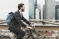 USA, New York, Brooklyn bridge,Side view of young businessman riding on bicycle — Stock Photo