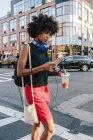 Portrait de jeune femme marchant dans la rue avec smartphone et boisson — Photo de stock