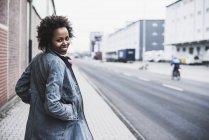 Mulher jovem sorridente na calçada olhando para a câmera — Fotografia de Stock
