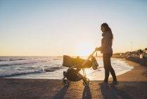Frau spaziert mit Kinderwagen am Strand bei Sonnenuntergang — Stockfoto
