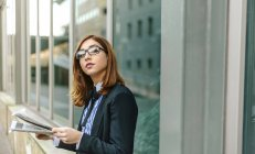 Businesswoman standing in front of wall and holding newspaper — Stock Photo