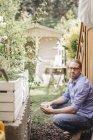 Mann mit Tasse Kaffee relaxen im Garten — Stockfoto