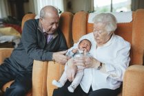 Great grandparents taking care of great granddaughter at home — Stock Photo