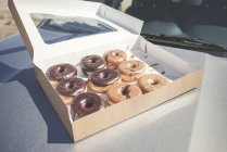 Doughnuts with different icings in a box on car bonnet — Stock Photo
